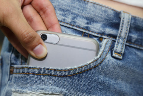 Security on the go: how to make mobile working safe. Photo shows a phone being pickpocketed from someone's pocket.