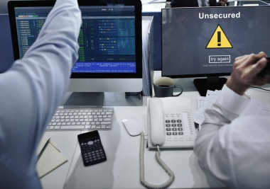 Is free antivirus effective? Picture shows two colleagues sat in front of their respective desktops. One is working, the other is displaying an error message, reading; 'Unsecured'.